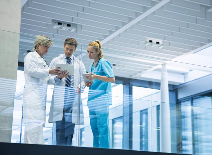 Medical team discussing over digital tablet in corridor