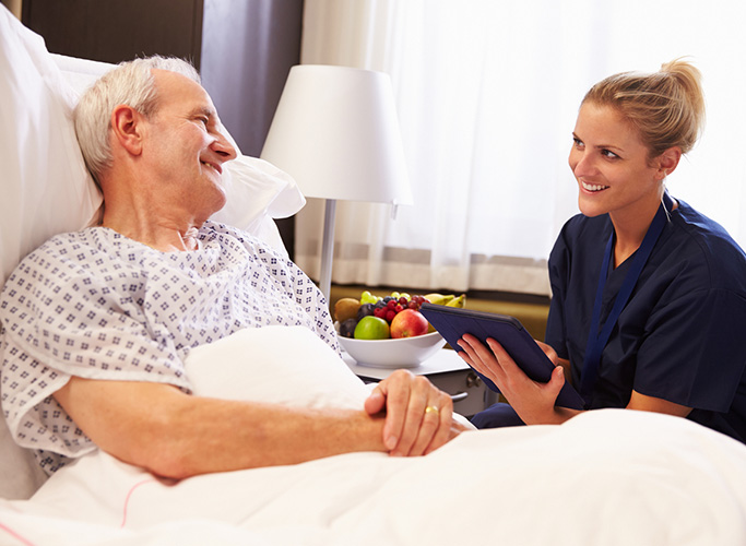 urse Talking To Senior Male Patient In Hospital Bed